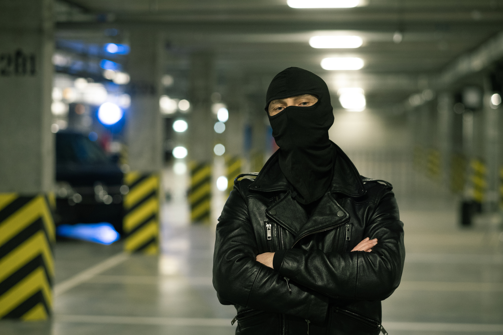 Contemporary criminal in black leather jacket and balaclava on head crossing arms by chest with parking area on background